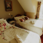 A bright, nicely decorated bedroom with a double bed and a single bed